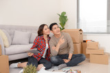 Happy young couple looking at blueprint planning new home interior design settling in, homeowners talking about remodeling ideas, discussing house architectural plan moving in apartment with boxes - 211768898