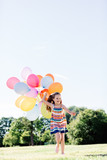 Young girl in a dress running with a bunch of balloons. - 211769065