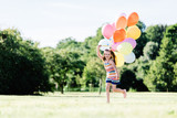 Young girl running on the grass field with balloons. - 211769084