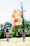 Two little girls holding a bunch of balloons together. - 211769270