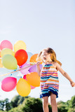 Happy girl running with a bunch of colorful balloons. - 211769477