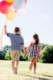 Young boy and a girl running with a bunch of colorful balloons. - 211769613