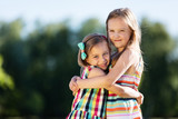 Two little girls hugging each other in the park. - 211770418