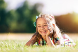 Little smiling girl laying on the grass field in the park. - 211770643