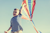 Little happy boy playing with a colorful kite - 211771275
