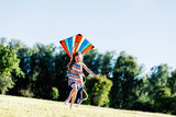Happy little girl holding a kite and running - 211771417