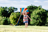 Happy girl running on the grass field with a colorful kite. - 211771487