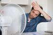 Leinwanddruck Bild - Sweaty man trying to refresh from heat with fan