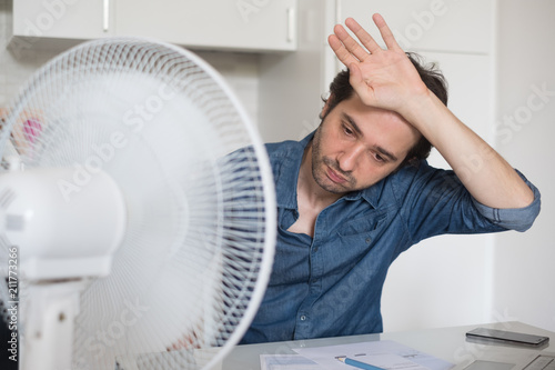 Sweaty man trying to refresh from heat with fan - 211773266