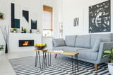 Real photo of a grey sofa standing in front of a wooden table in living room interior with posters on the walls, striped rug and bio fireplace