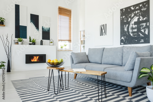 Real photo of a grey sofa standing in front of a wooden table in living room interior with posters on the walls, striped rug and bio fireplace - 211774442