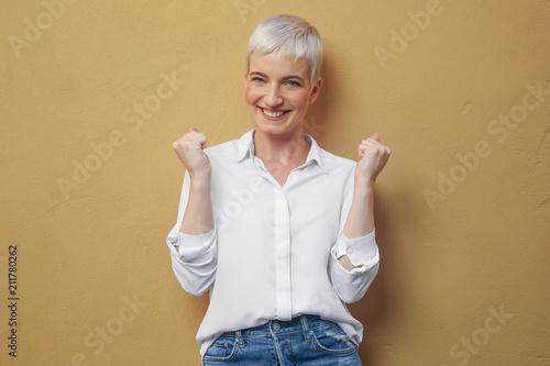 canvas print picture Junge blonde Frau an der Wand / lächelnd