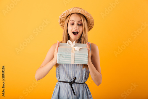 Portrait of a cheerful young blonde woman in summer hat