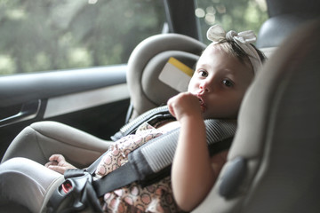 Cute baby sitting on the booster seat in the car