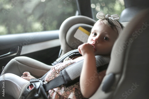 Fototapeta Cute baby sitting on the booster seat in the car