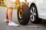 The man changes the tire to a broken car - 211794691
