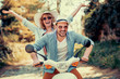 Happy young couple riding a scooter