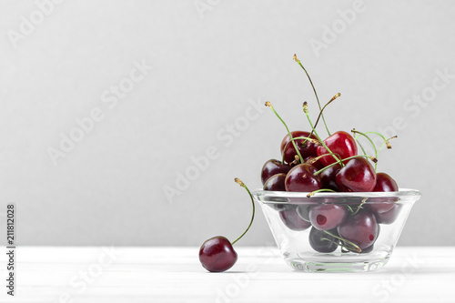 Fotobehang Kersen Red sweet cherries in a glass bowl on a white wooden table close-up..