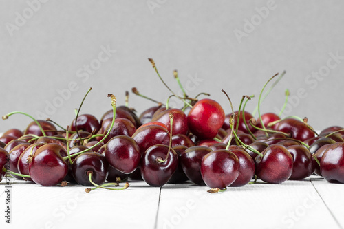 Aluminium Kersen A handful of red cherries on a white wooden table in a crisp plan..