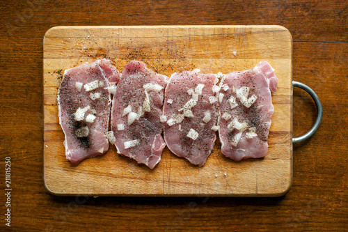 Aluminium Steakhouse steaks of pork with onions and peppers on a cutting board. View from above