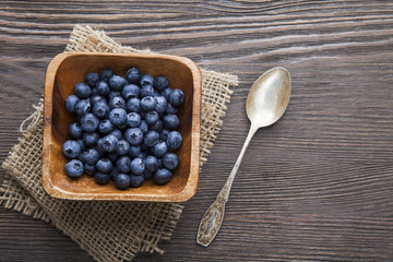 heap ripe sweet blueberries and spoon on wooden table top view