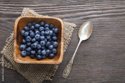 heap ripe sweet blueberries and spoon on wooden table top view - 211824044