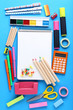 School supplies with blank sheet of paper on blue background