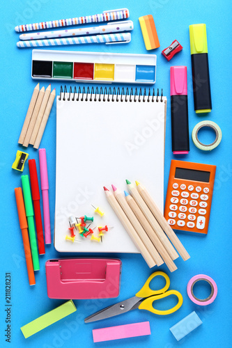 School supplies with blank sheet of paper on blue background - 211828231