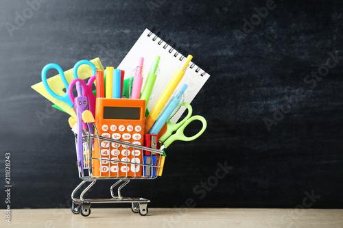 Fototapeta School supplies in shopping cart on blackboard background