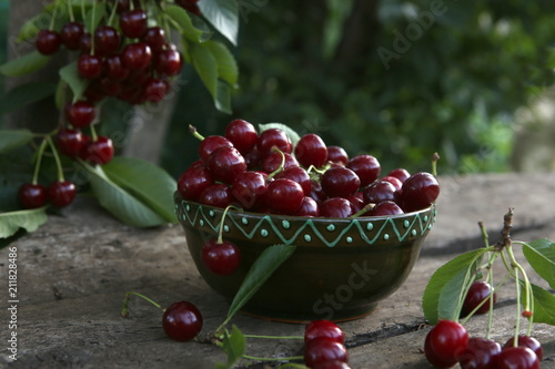 Foto Murales Freshly picked cherries in bowl on wooden table in garden.  Fresh ripe cherries harvested in bowl and cherry tree branch with berries in summer garden.