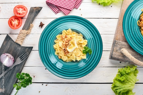 Fototapeta Farfalle pasta with brie cheese and nuts. Italian cuisine. On a wooden background. Top view. Copy space.