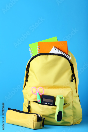 Yellow backpack with school supplies on blue background - 211829669