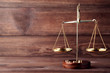 Leinwanddruck Bild - Scales of justice on brown wooden table