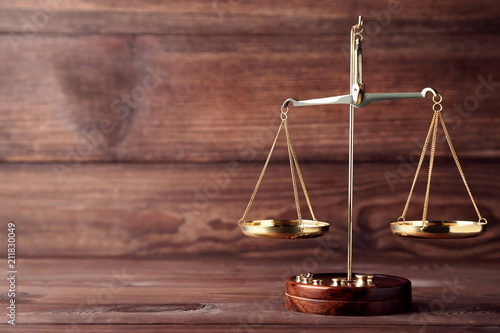 Leinwanddruck Bild Scales of justice on brown wooden table