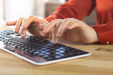 Womans hands on pc wireless keyboard. Gentle female hands with nude manicure slightly lifted above keyboard in process of typing.