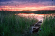 Wooden boat on the lake at sunset