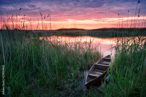 Wall mural Wooden boat on the lake at sunset