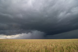 Supercell thunderstorm passes by a dry wheat field, releasing an intense core of rain and hail. - 211841899