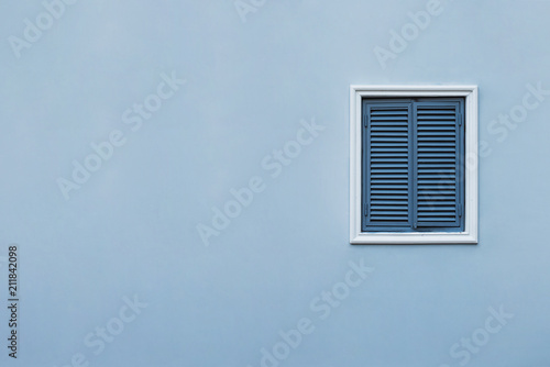 Blue wall of the house with a closed window right and details. © YM studio