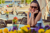 Portrait of a happy charming brunette girl wearing trendy clothes is enjoying summer day while sitting on a terrace in outdoors cafe, looking at a camera. - 211843297