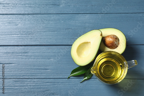 Leinwanddruck Bild Gravy boat with oil and ripe fresh avocado on wooden table, top view