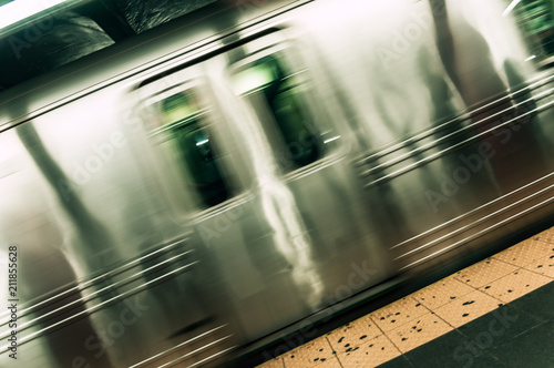 A fast moving subway car passing by a station in New York City