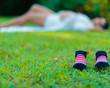 Baby booties in close-up with silhouette of pregnant woman in the background