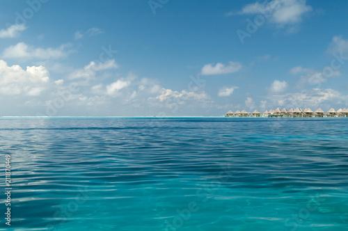 Spokojna woda w lagunie na Bora Bora pod jasnym, niebieskim niebem. Na horyzoncie jest ciąg bungalowów na palach nad wodą. Bora Bora, Polinezja Francuska.
