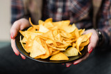 tortilla nacho chips food recipe. woman hand offering a plate of natural fried crisps - 211872649