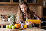 child health and development. useful and tasty drink. vitamin orange juice for balanced nutrition. little girl pouring fresh fruit beverage from a bottle - 211872850