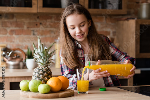 Fototapeta child health and development. useful and tasty drink. vitamin orange juice for balanced nutrition. little girl pouring fresh fruit beverage from a bottle