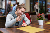 Male tourist with long hait sitting at street cafe with mobile phone. Concept of advantageous tariff plan, midern technology and leisure time. - 211879444