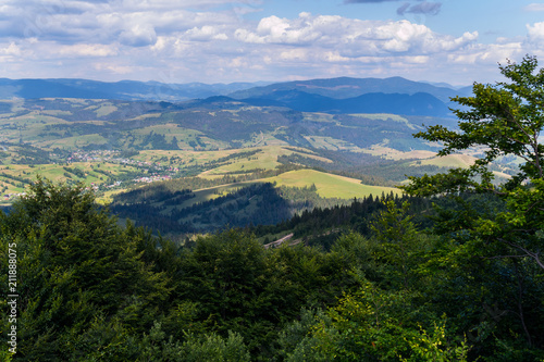 Thick branches of trees in the foreground and a mountain range with a blue sky in the background - 211888075