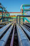 Perspective de tuyaux chromés sur fond de ciel bleu dans une usine pétrochimique - 211893653
